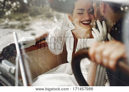 Elegant Gorgeous Bride Smiling And Handsome Stylish Groom Kissing Her In Car. Unusual Luxury Wedding