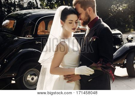 Elegant Gorgeous Bride And Handsome Stylish Groom Gently Hugging On Background Of Black Car. Unusual