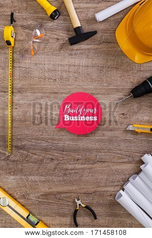 Helmet, flashlight and tape measure. Build your business speech bubble. Architecture plans, knife and protective glasses. Building level, hammer.
