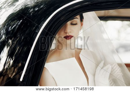Gorgeous Elegant Bride Posing In Stylish Retro Black Car, Sitting Inside In Saloon.  Luxury Wedding