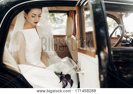Gorgeous Elegant Bride Posing In Stylish Retro Black Car, Sitting Inside In Saloon Holding Bouquet O