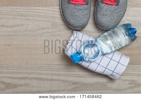 Fitness gym equipment. Sneakers, water bottle with towel. Workout footwear. Sport trainers with pink shoelace.