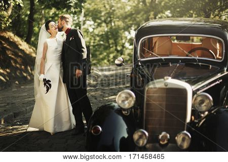 Elegant Stylish Groom Kissing Gently Gorgeous Bride, At Black Car In Light In Park. Unusual Luxury W