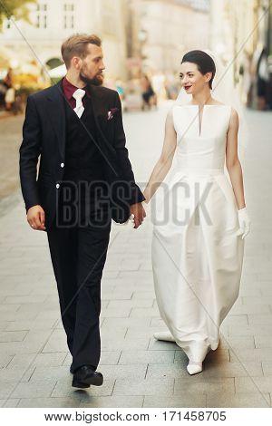 Luxury Wedding Couple Holding Hands And Walking In City Street. Elegant Gorgeous Bride And Stylish G