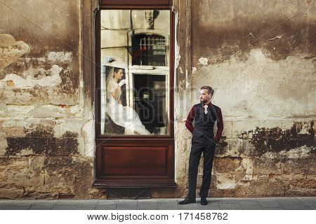 Elegant Gorgeous Bride  Drinking Coffee In Window And Stylish Groom Posing At Building In Street Out