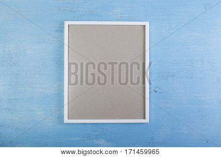 Blank photo frame on blue wood background. Painted scraped wooden board. Grunge plywood texture or pattern.