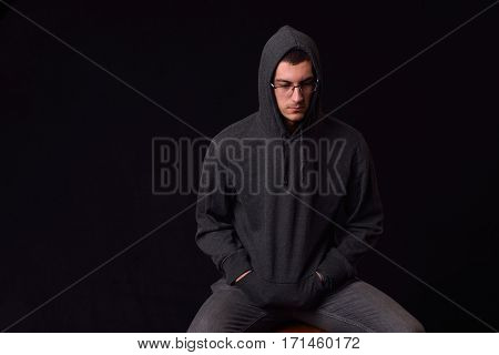 Confident Young Man Wearing Glasses And Black Hoodie Posing On A Black Background. Studio Shot.