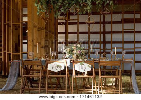 The sun shines Decoration wedding table before a banquet in a wooden barn. Wedding party. Vintage Style.