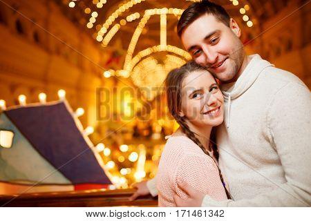 Beautiful couple at shopping mall among lights