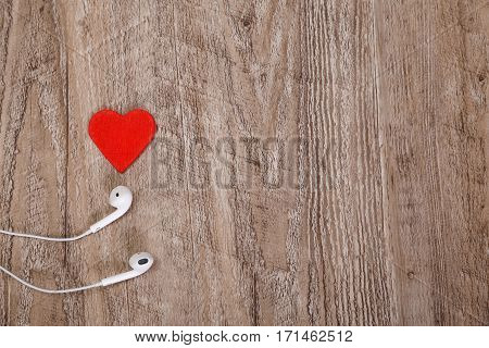 White headphones with red heart. Love listening music. Sound earphones lying on wooden rustic background.