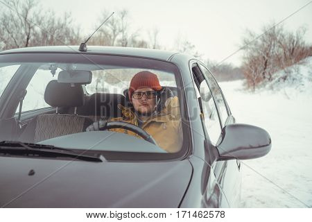 Man driving car using smart phone in car in winter day