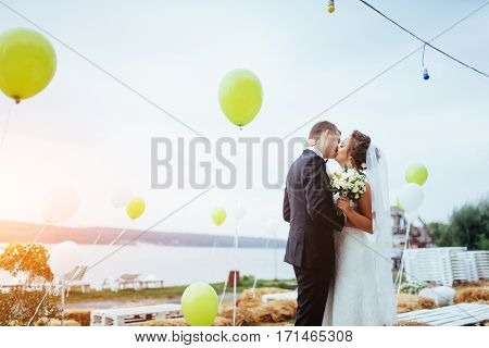 Beautiful young couple kissing wedding, blonde bride with her groom and flower in the park in summer solar haze, and a lot of balloons