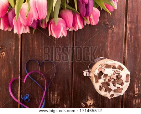 Cup of coffee with heart and colourful tulips