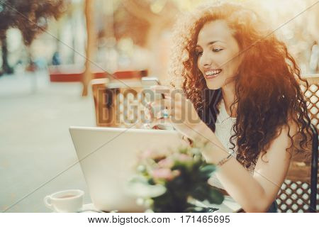 Smiling beautiful white caucasian girl with black curly hair sitting in street cafe and texting message on her phone happy attractive woman browsing site on her smartphone with opened laptop in bar