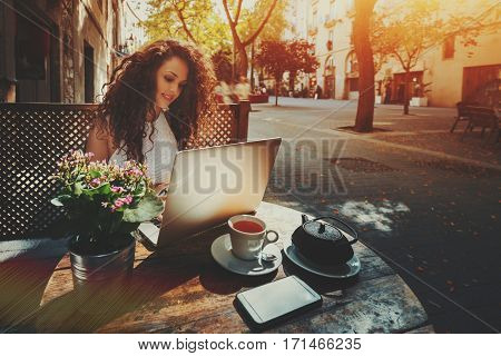Attractive beautiful white caucasian freelancer girl with curly black hair is sitting in street cafe with cup and teapot of tea in front of wooden fence and working on her modern laptop on sunny day