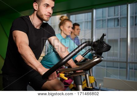 Young athletes on stationary bike at gym