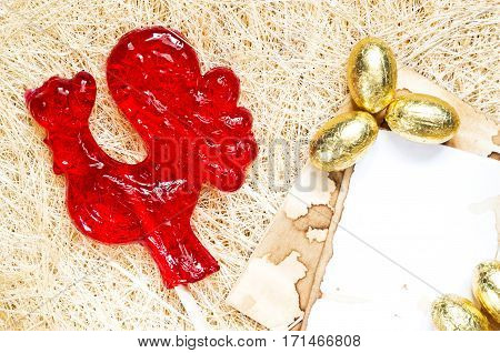 A red rooster lollipop with golden eggs background. The rooster is a symbol of 2017 and a sign of the Chinese horoscope.