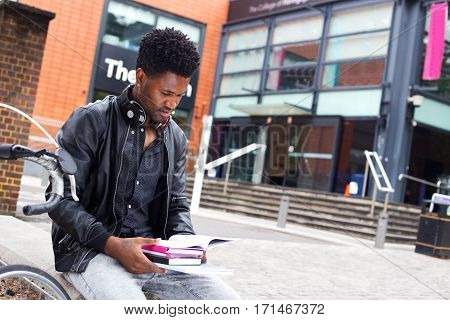 student sitting outside his college reading text books