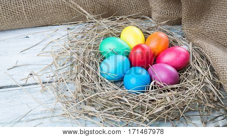 Colorful easter hen eggs in hay on wooden background. Easter eggs in straw nest