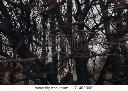 Stylish Hipster Man And Woman Under Branches Hugging Gently, Tender Touch In Autumn Park. Sensual At