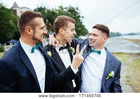 Confident smiling handsome groom in black suit with two groomsman