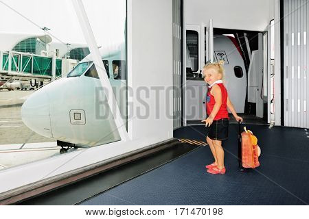 Happy baby girl wait for boarding to flight in departure gate from airport transit hall and looking through window at airplane. Active lifestyle travel by air with child on family summer vacation.