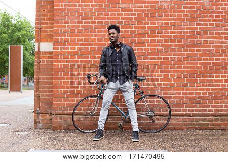 young man with his bike leaning against a wall