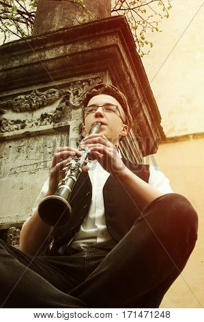 Stylish Hipster Sitting Man Playing Clarinet  On Background Of Old City Street, Close Up