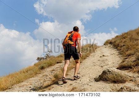 Man walking up steep mountain summer day