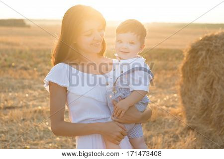 Mother And Son. Hay Stack Or Bale On Yellow Field.