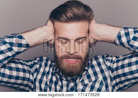Angry Bearded Man With Closed Eyes Covering Ears With Hands