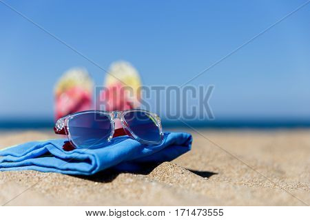 Sunny sea shore with sunglasses on plaid on background of sea and of flip flops