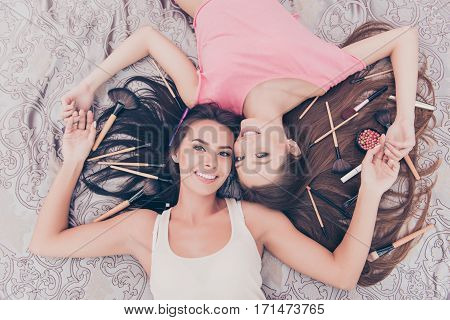 Top View Of Two Pretty Girls Lying With Cosmetics And Makeup Brushes