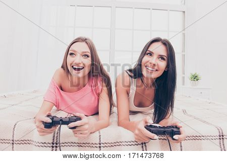 Happy Excited Girls Lying In Bedroom And Playing Video Game