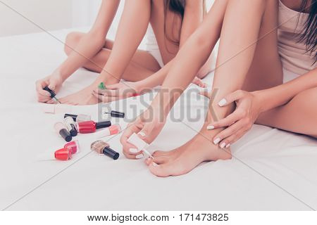 Close Up Of Two Young Women Painting Nails On Foot