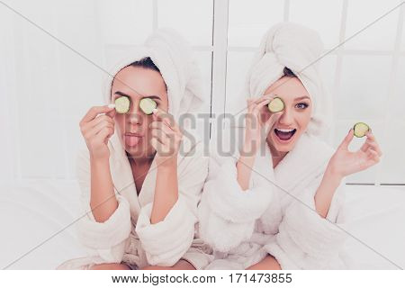 Funny Young Girls In Bathrobes Making Mask With Cucumber And Having Fun