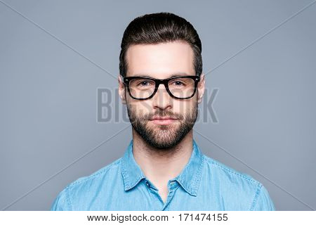 Portrait Of Handsome Young Bearded Man In Glasses On Gray Background