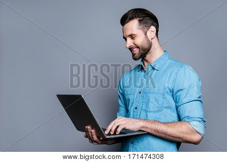 Smiling Cheerful Young Man  Holding Laptop And Typing