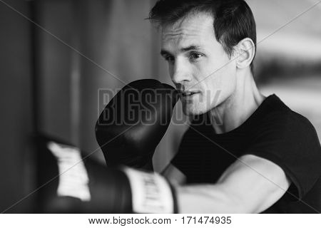 Black-white photo of young boxer near punching bag in gym