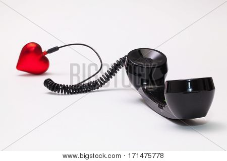 Old phone reciever and cord connection with red heart. Love hotline concept.
