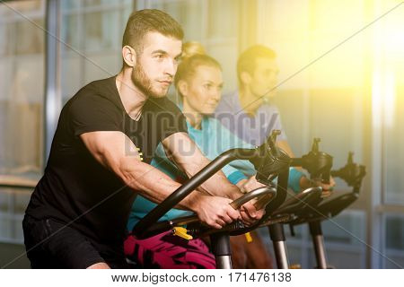 Young sportsmens on stationary bike in fitness center in sport clothes