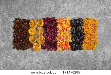 Assortment of dried fruit and candied fruit. Fruits figs prunes raisins papaya pineapple cranberries are laid out in rows on gray concrete background. Top view. Flat lay.