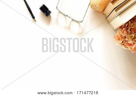 Top view of a charming desk top with vintage book stack, flowers, eyeglasses and pen and ink framing open white space