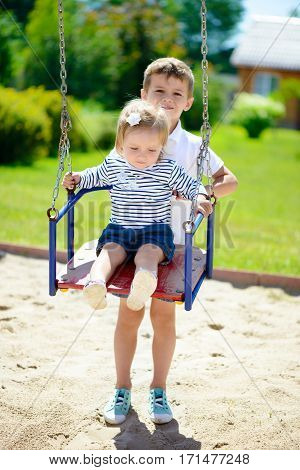 Little cute brother and sister swinging in summer park
