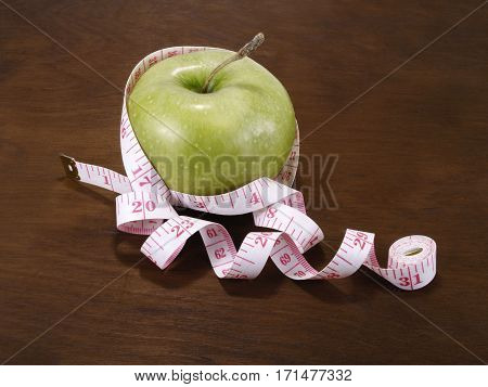 ?resh green apple on a wooden table with measure close up
