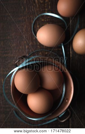 Chicken eggs with ribbons on the wooden table