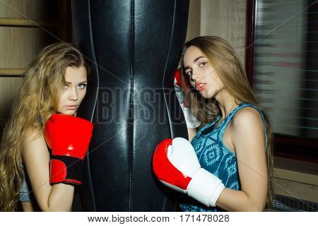 Two pretty girls or beautiful women cute sexy fit female boxers sparring partners in sportswear and red boxing gloves training to punch with punching bag in fitness gym