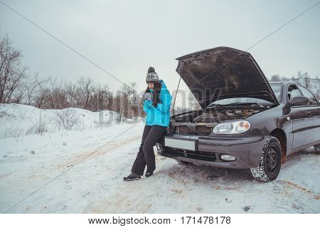 Winter car breakdown - woman call for help, road assistance worm up with tea