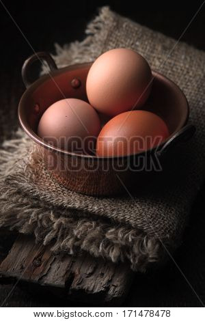 Cooper bowl with chicken eggs on the wooden table vertical