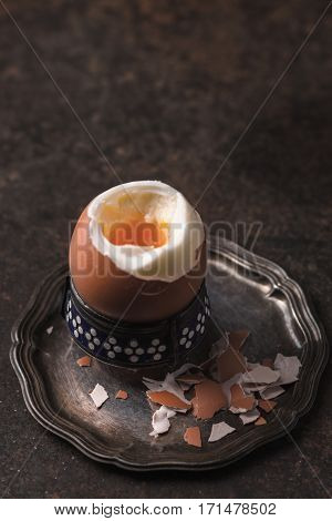 Soft-boiled egg on the metal background vertical